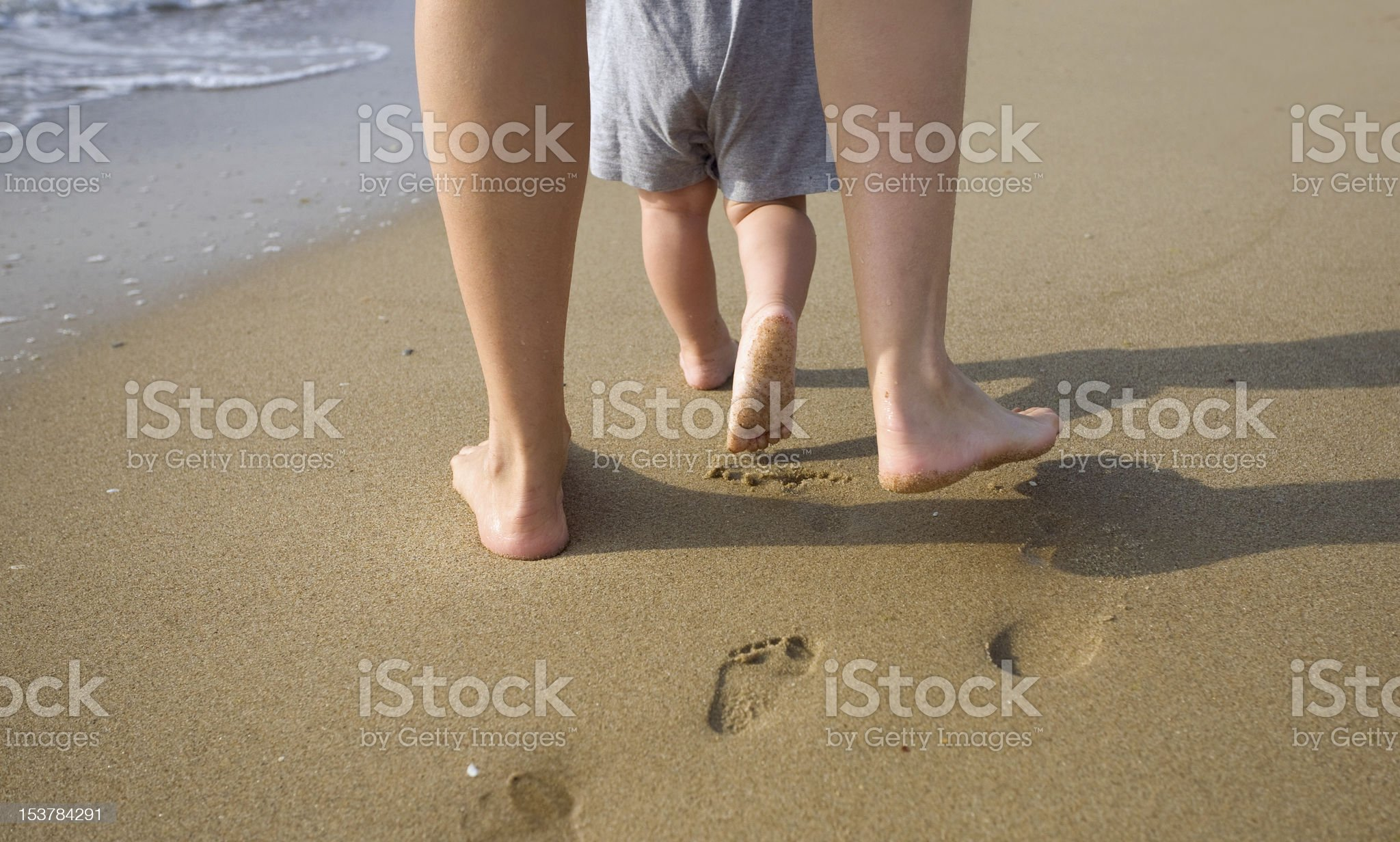 Mother and child walking on a sandy beach royalty-free stock photo