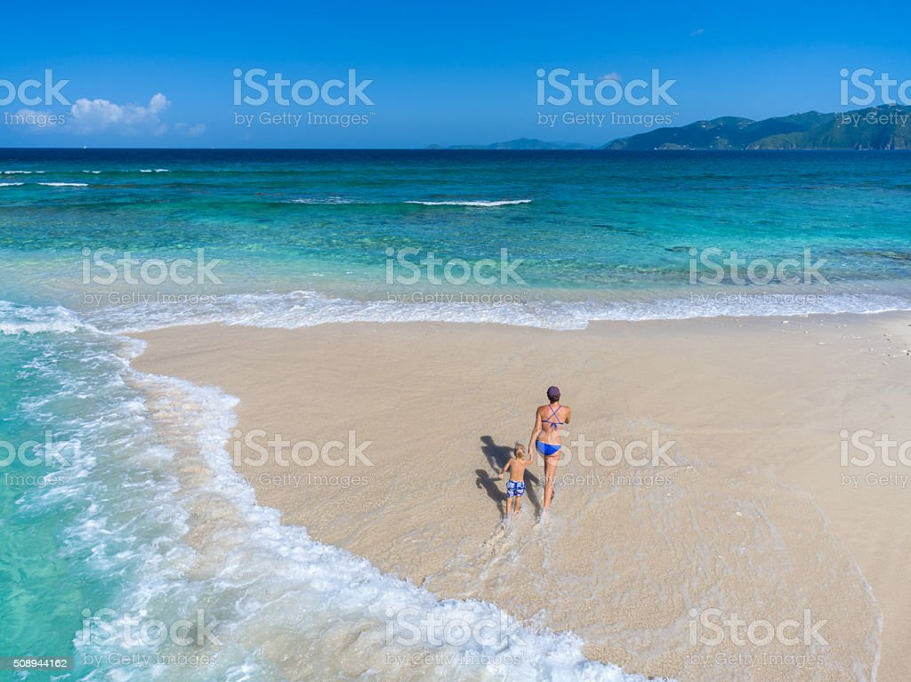 Mother and child walking on tropical beach stock photo