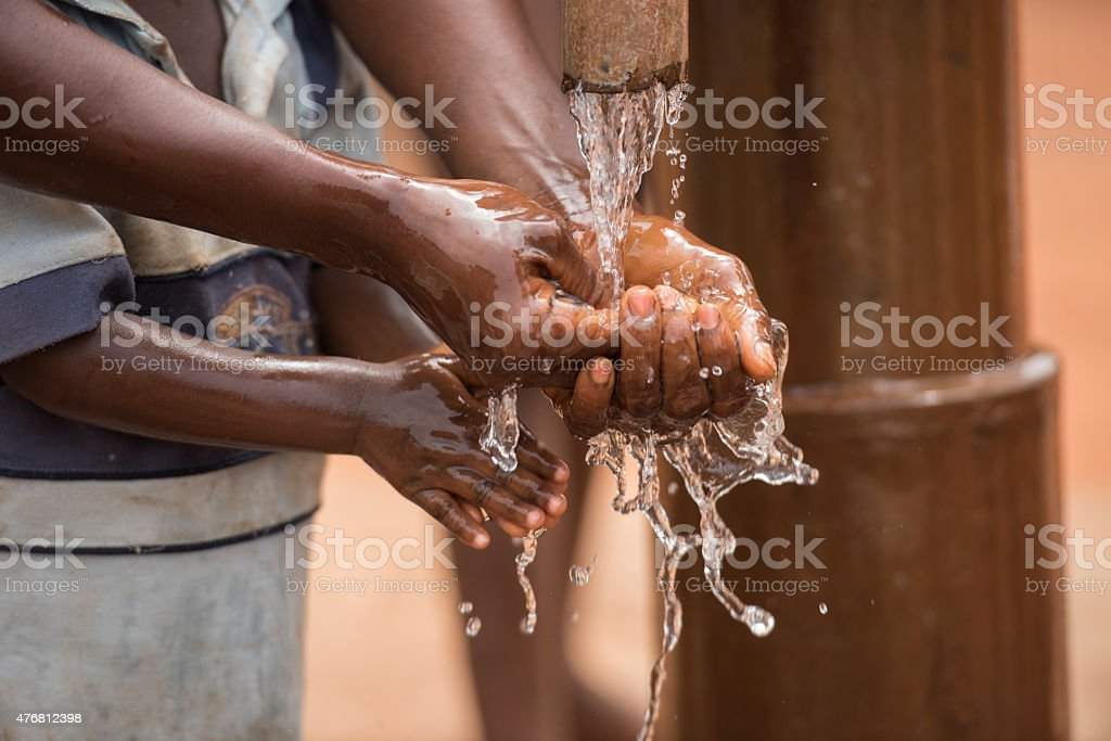 Mother and child washing hands with clean water stock photo