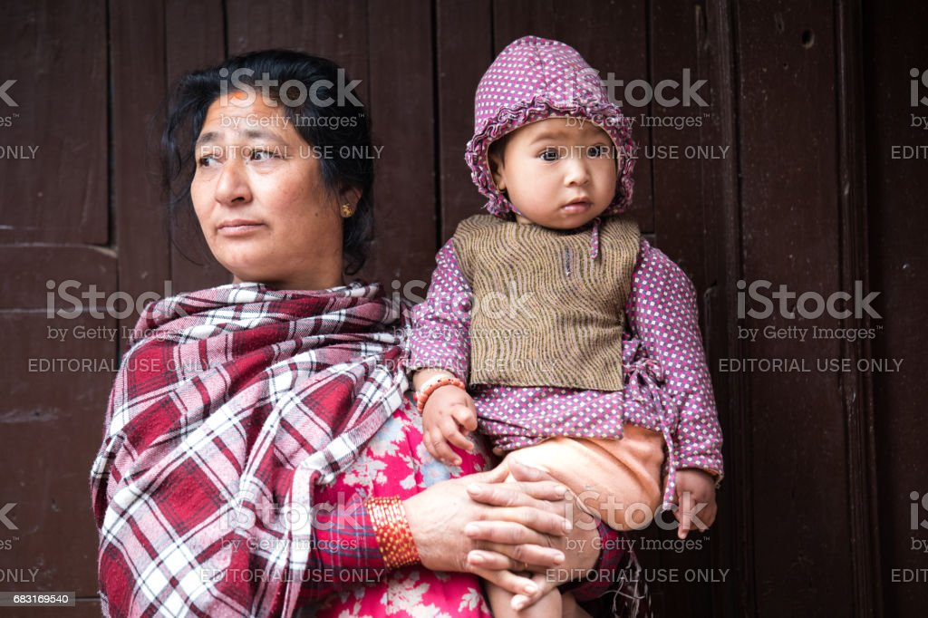 Mother and child watching ceremony procession. stock photo