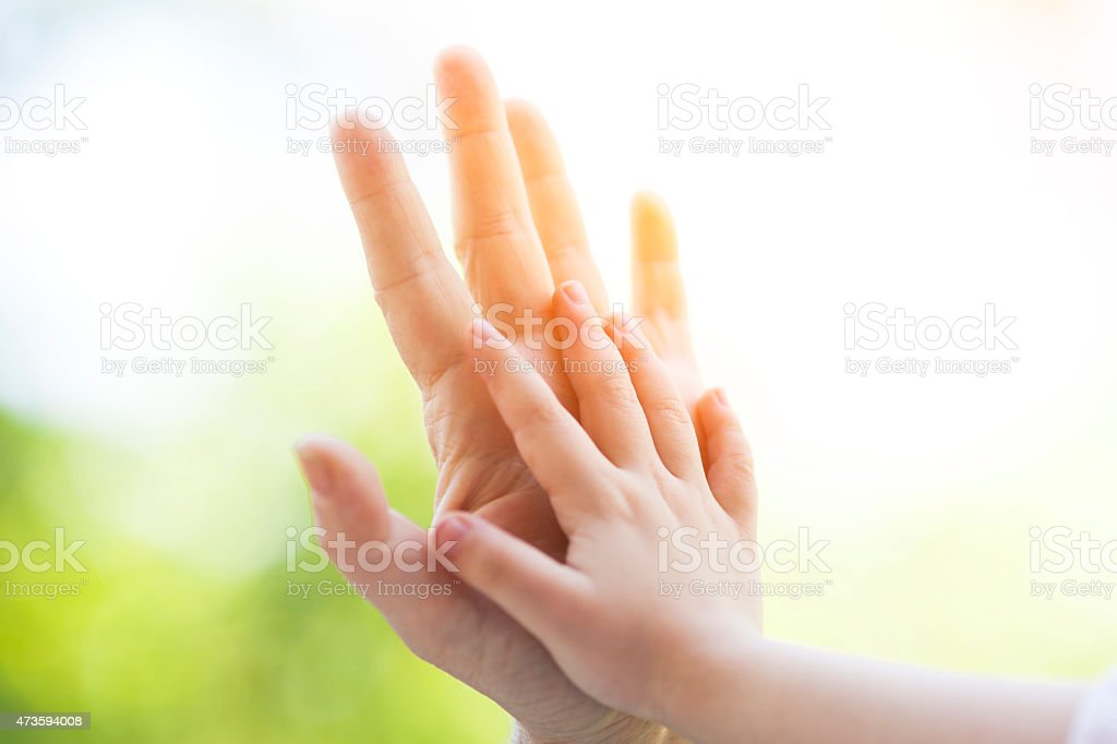 Mother and child with palm to palm hands stock photo