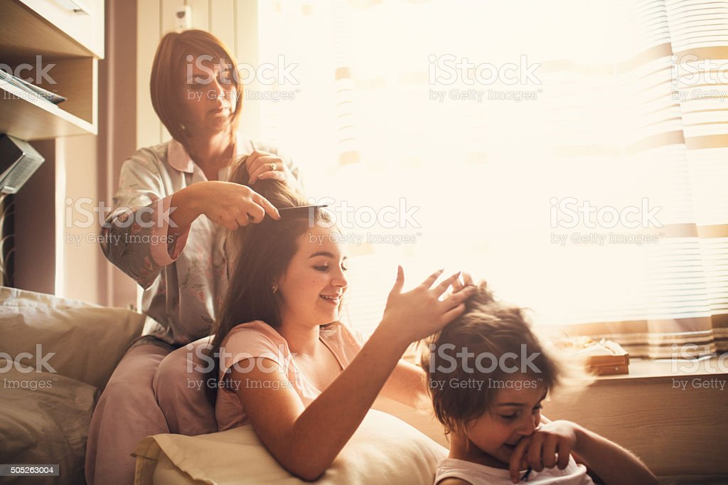 Mother and children brushing hair stock photo