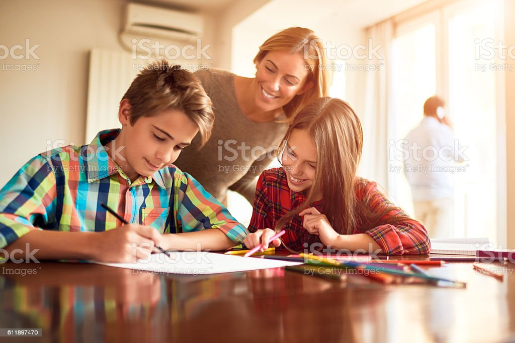 Mother and children doing homework stock photo
