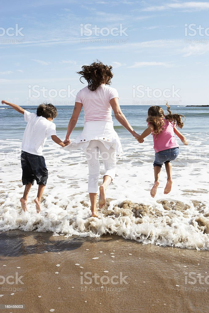 Mother and children having fun on the beach stock photo