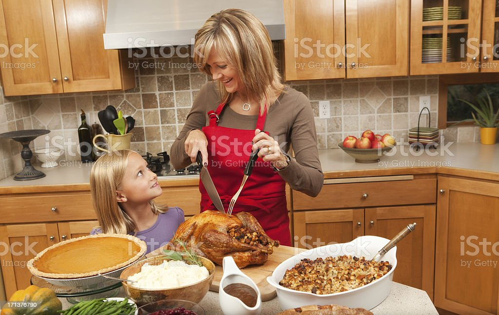 Mother and Children Helping to Serve Thanksgiving Turkey Hz royalty-free stock photo