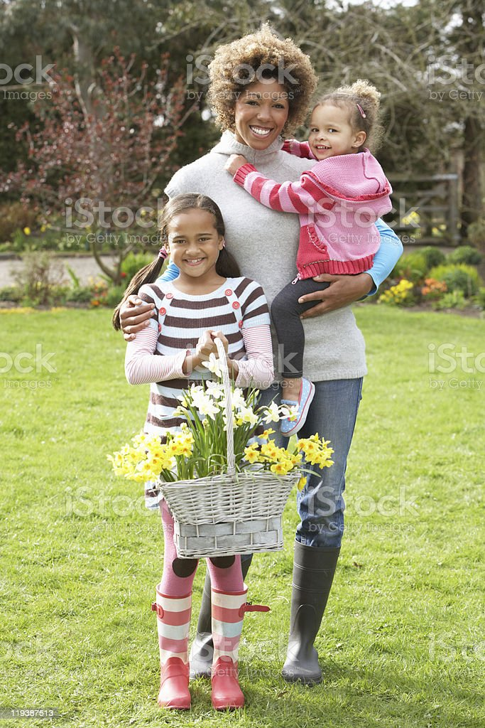 Mother And Children Holding Basket Of Daffodils In Garden royalty-free stock photo