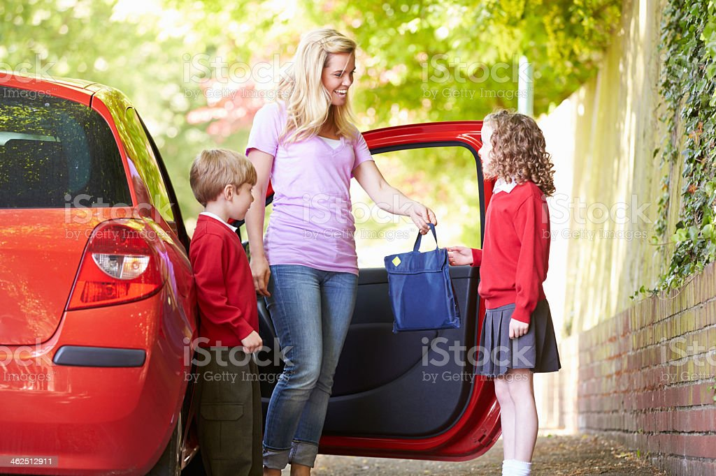 Mother and children in school uniform next to red car stock photo