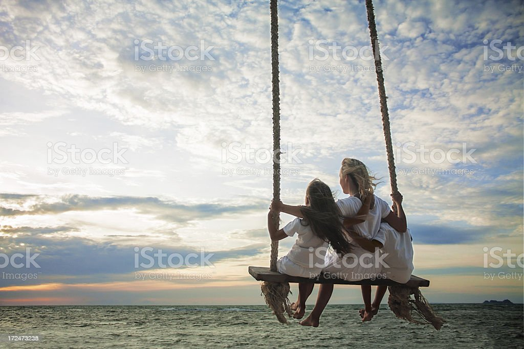Mother and children on swing stock photo