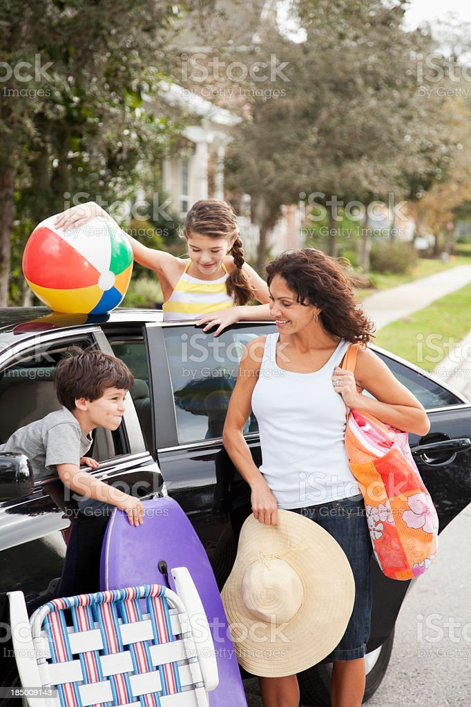 Mother and children packing car for trip to beach stock photo
