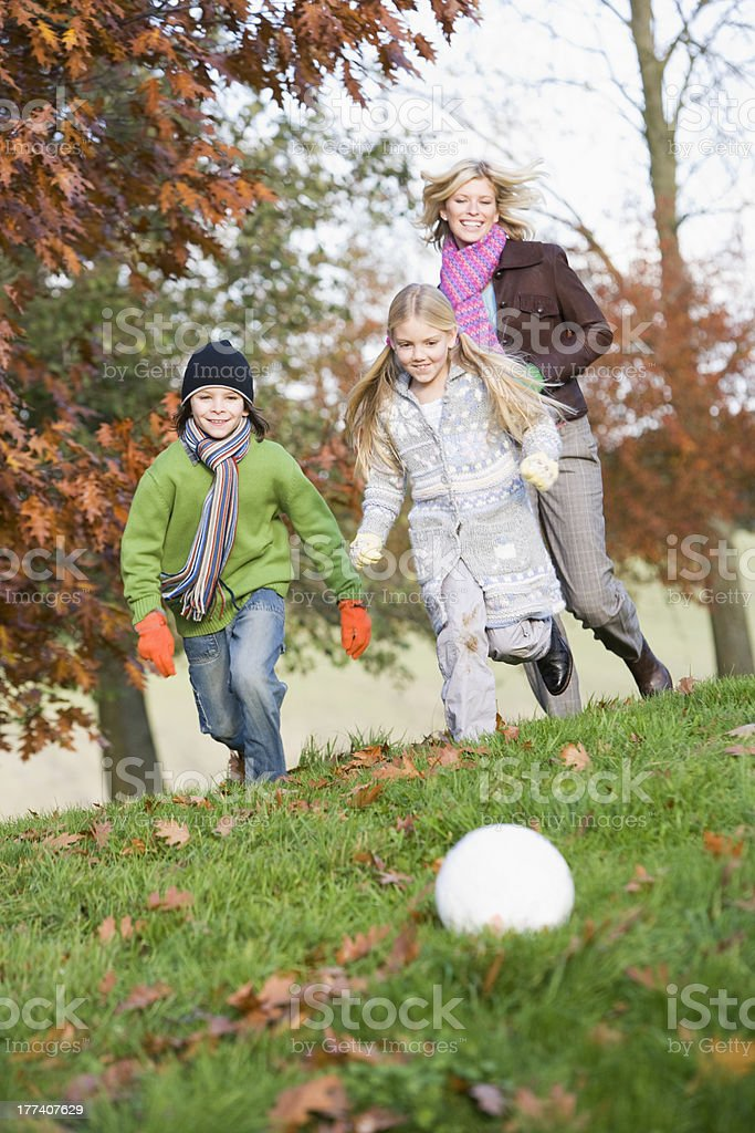 Mother and children playing football in garden royalty-free stock photo