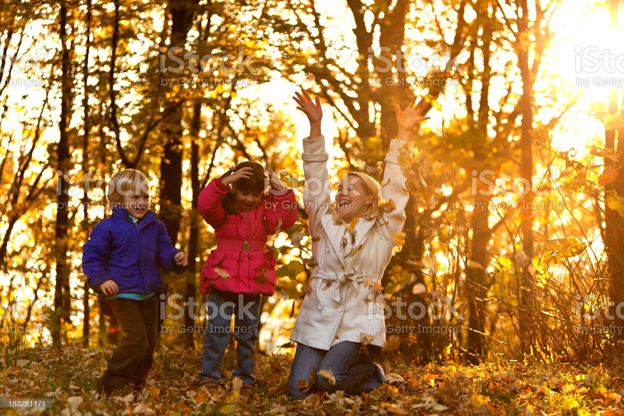 Mother and children playing with leaves in an autumn forest royalty-free stock photo