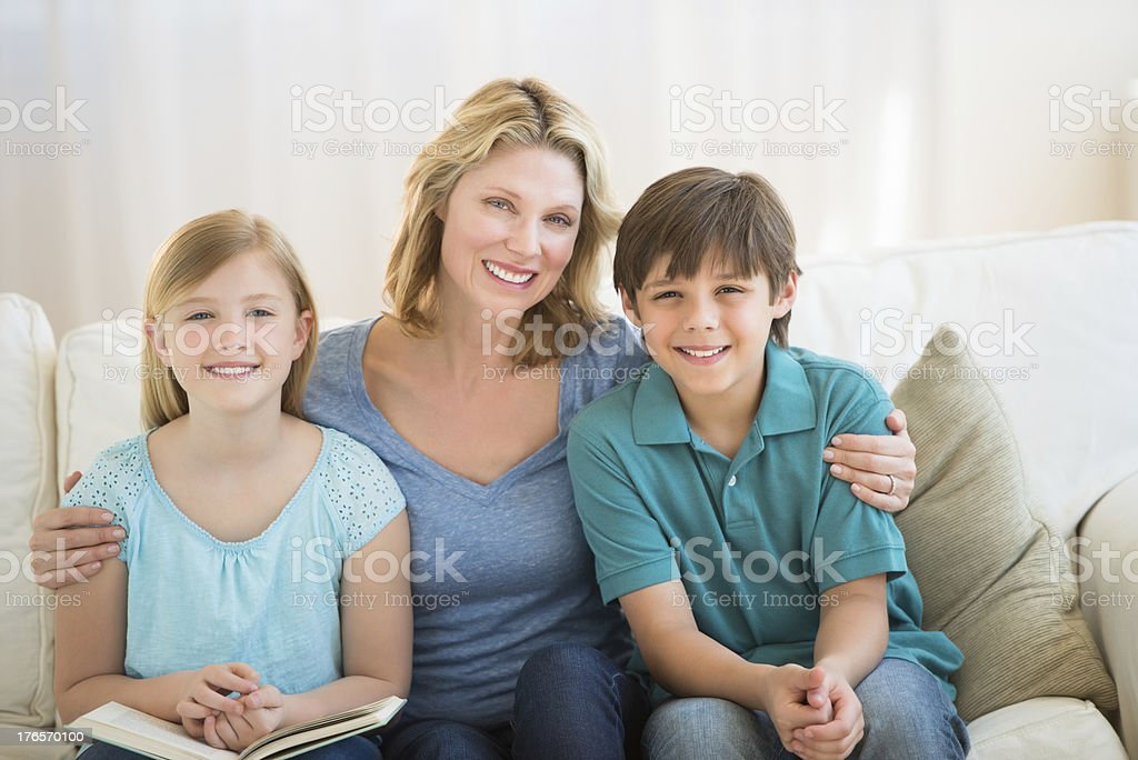 Mother And Children Smiling Together On Sofa stock photo
