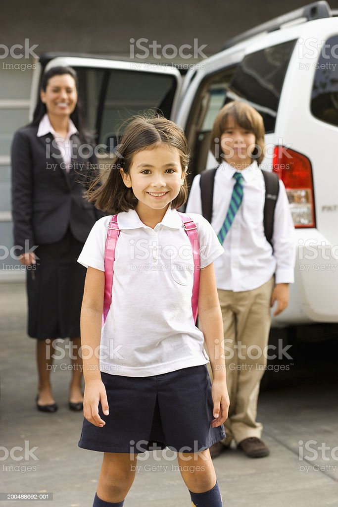 Mother and children (6-10) standing by car royalty-free stock photo