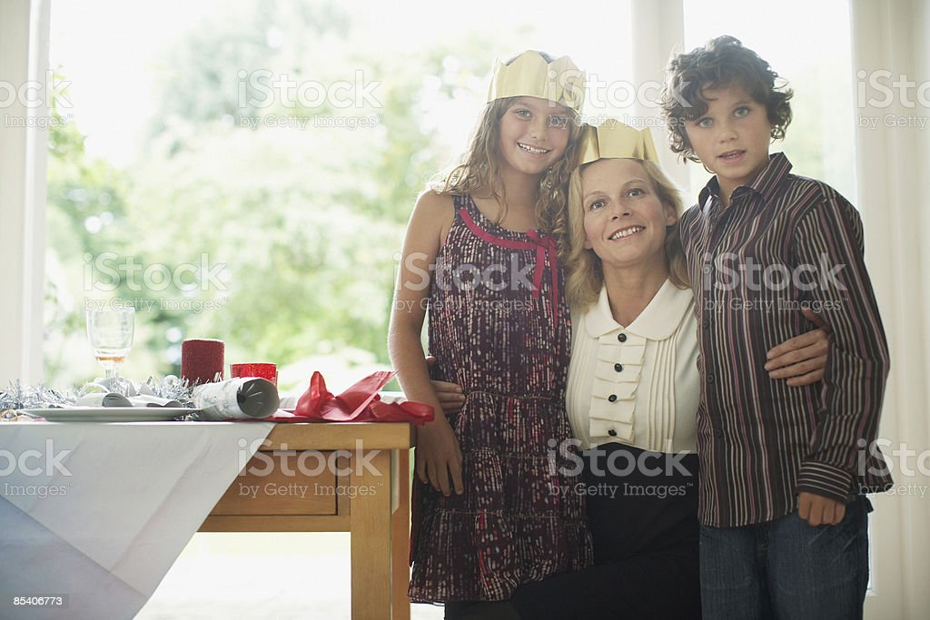 Mother and children wearing Christmas crowns stock photo