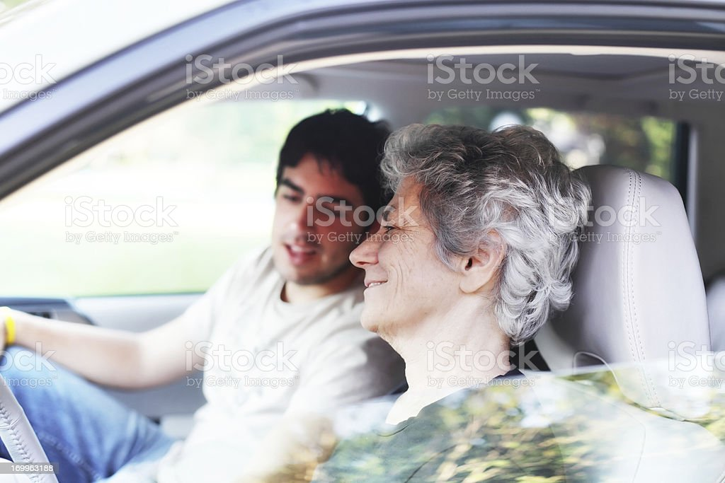 Mother and College Son Sharing Music in Car royalty-free stock photo