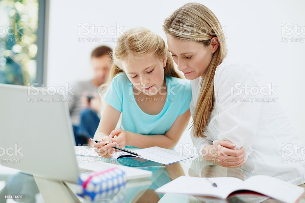 Mother and cute daughter studying with family in background royalty-free stock photo