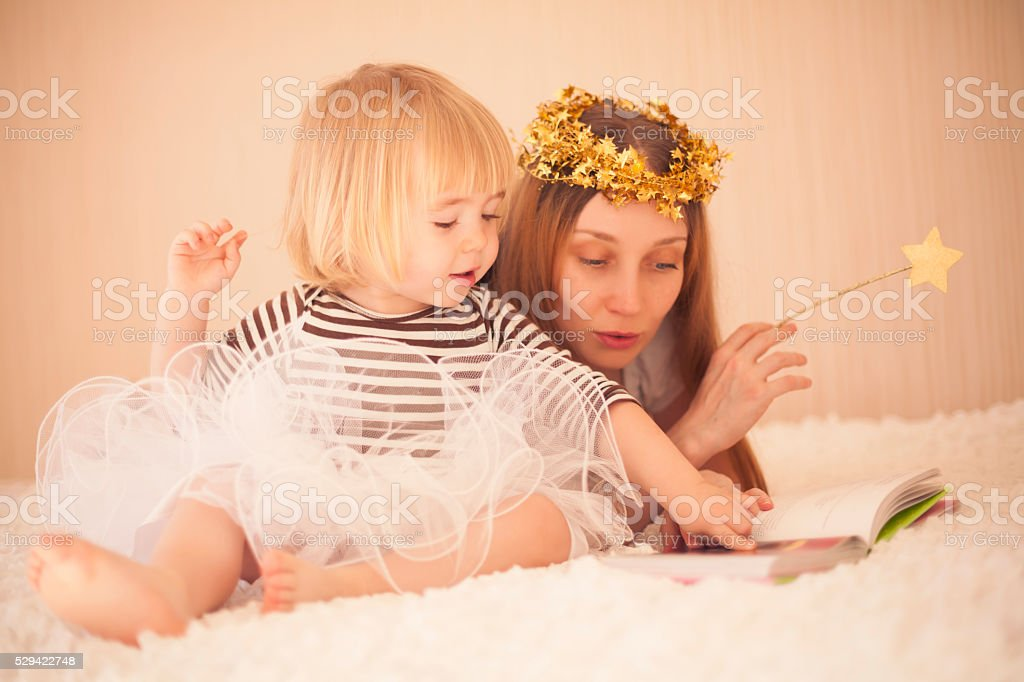 Mother and cute little girl reading in bed stock photo