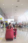 Mother and cute toddler girl pulling together a suitcase