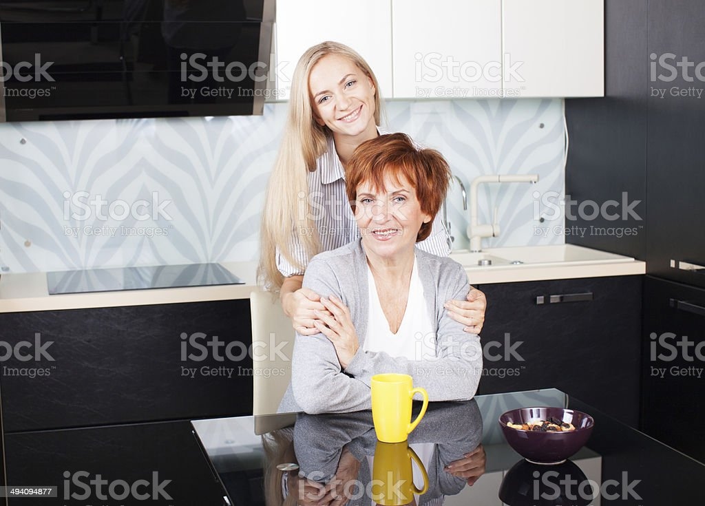 Mother and daudhter talking on the kitchen royalty-free stock photo