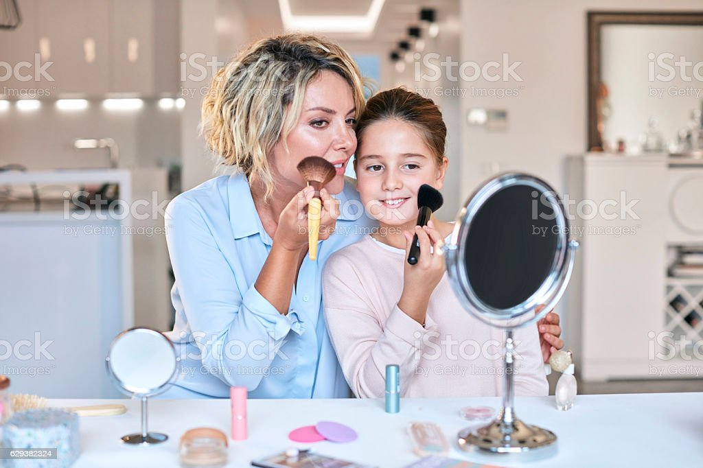 Mother and daughter applying makeup stock photo