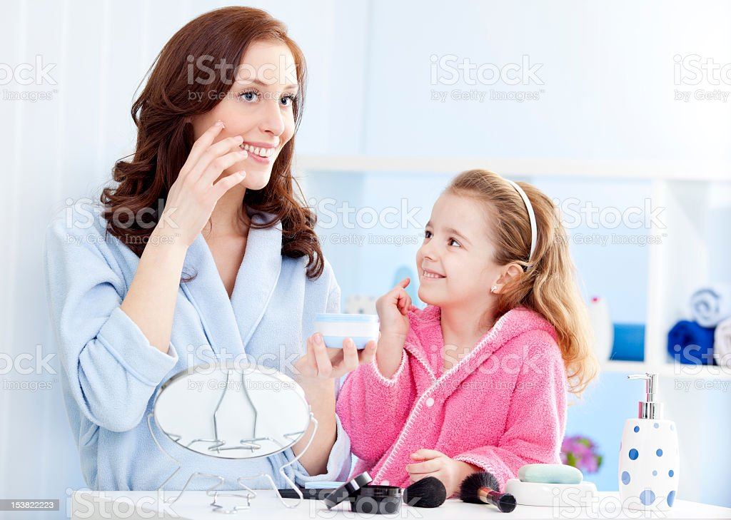 Mother and daughter applying moisturizer face cream. stock photo