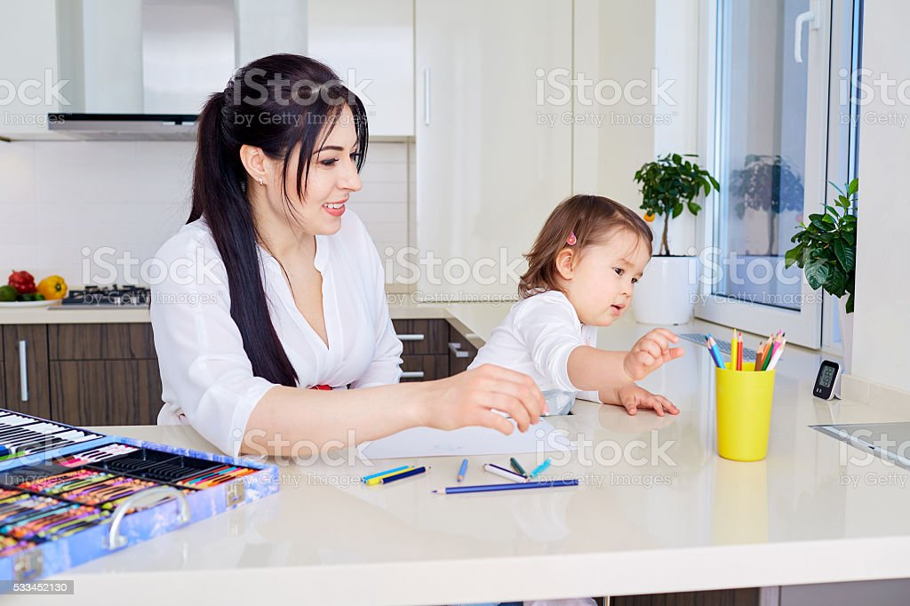 Mother and daughter are having fun while drawing at home. stock photo