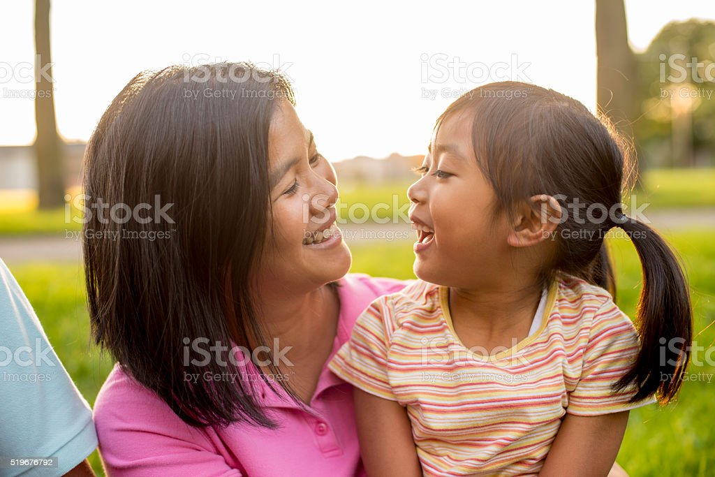 A mother and daughter are laughing together at the stock photo