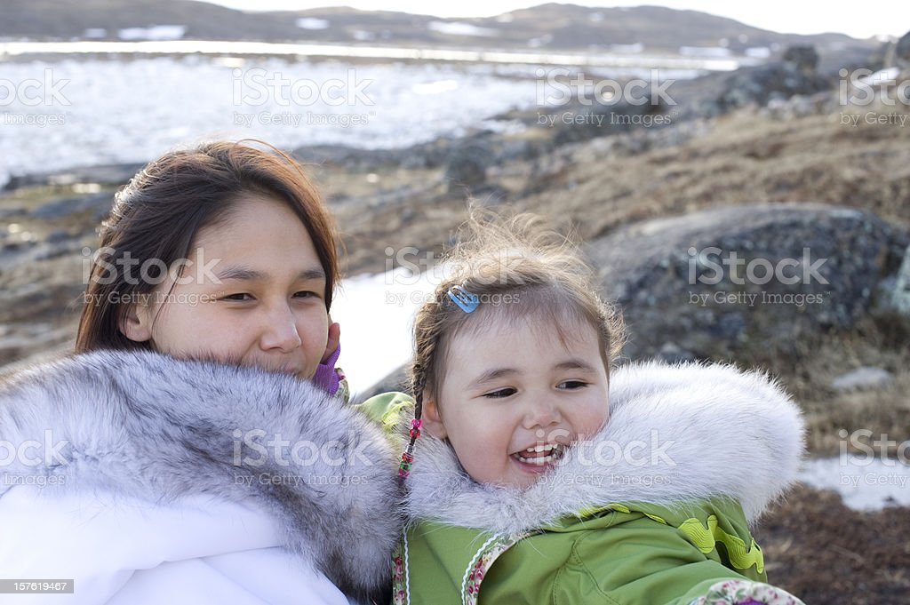 A mother and daughter are on an island smiling and pointing royalty-free stock photo