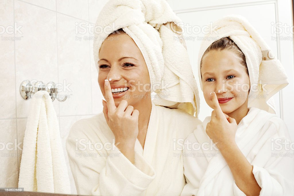 Mother and daughter are putting on face cream. royalty-free stock photo