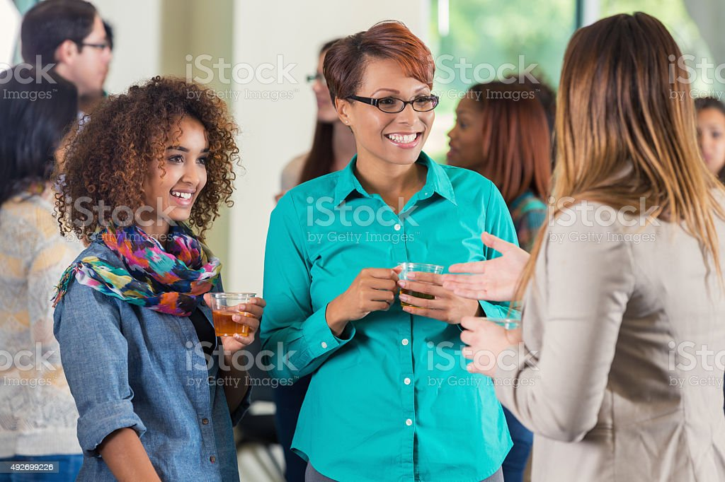 Mother and daughter at college meet and greet party stock photo