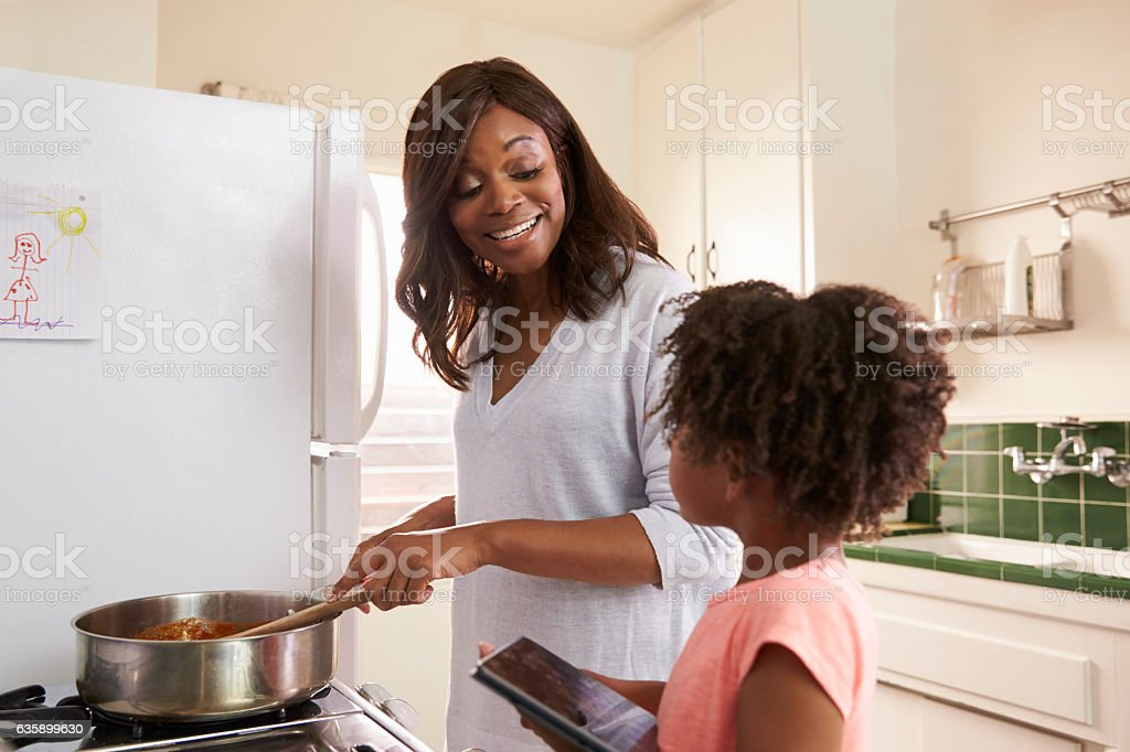 Mother And Daughter At Home Preparing Meal In Kitchen stock photo