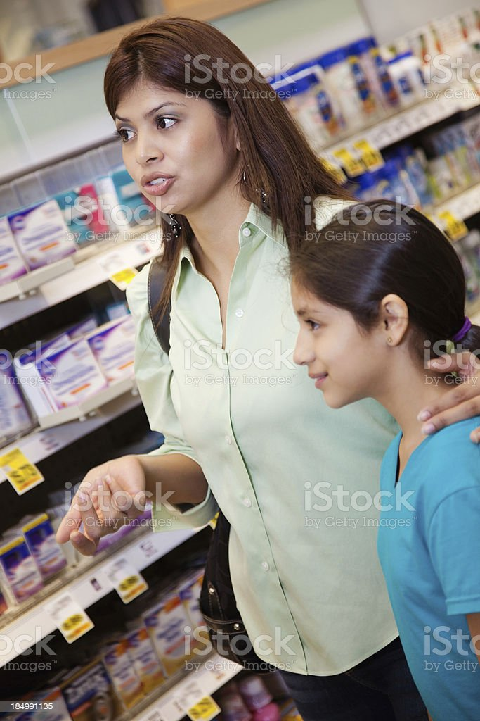 Mother and daughter at pharmacy talking to someone royalty-free stock photo