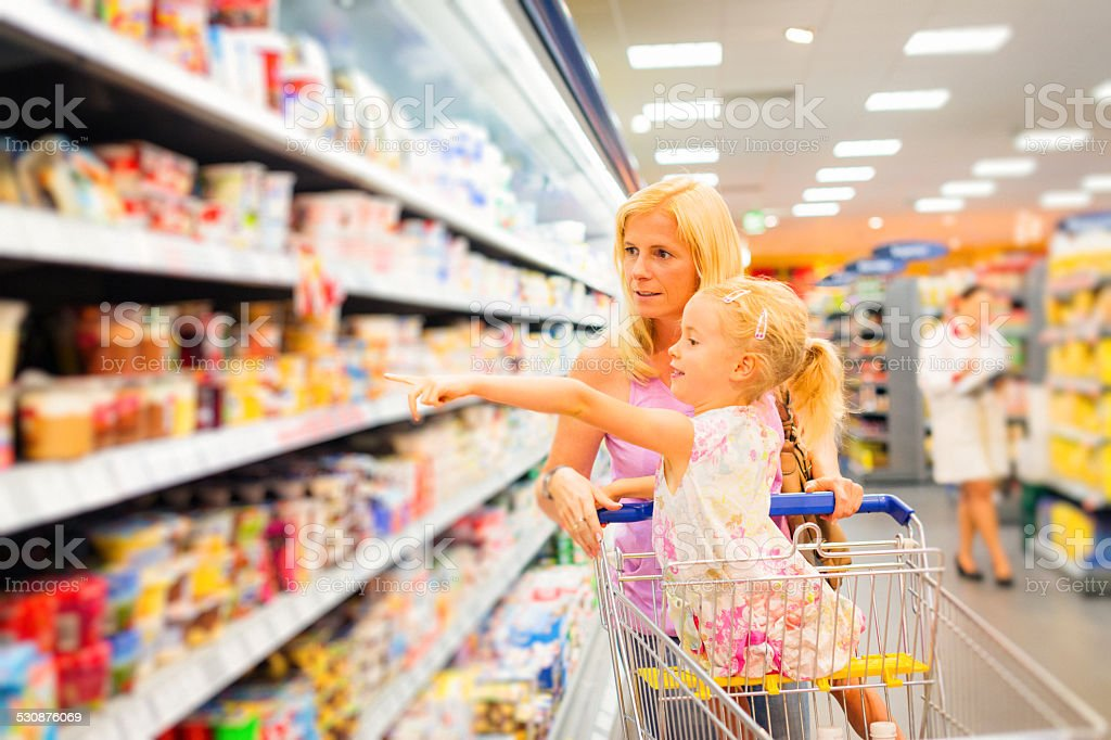 mother and daughter at the supermarket stock photo