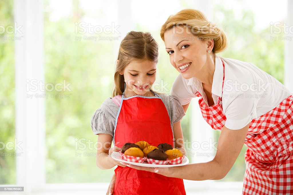 Mother and daughter baking cakes stock photo