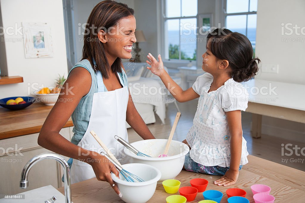Mother and daughter baking cupcakes in kitchen stock photo