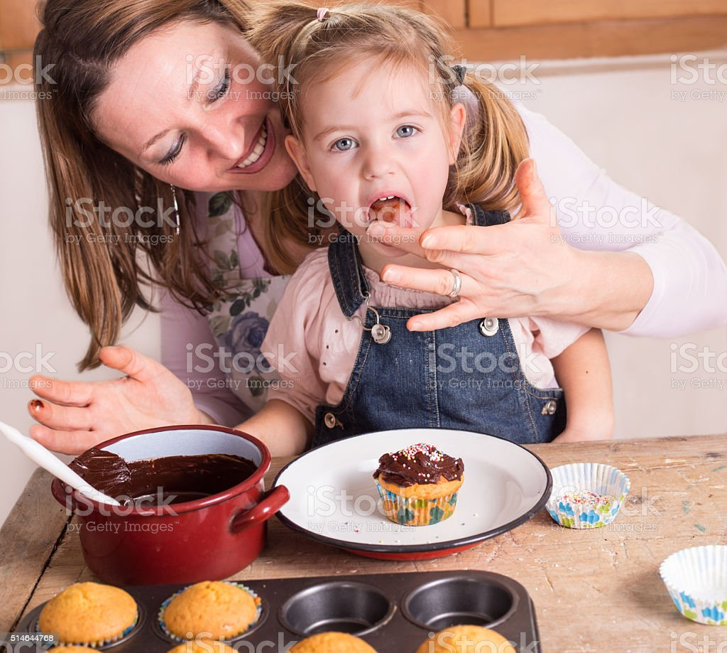 mother and daughter baking cupcakes stock photo