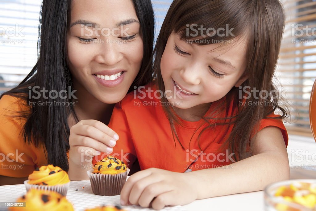Mother and daughter baking halloween cupcakes stock photo