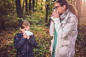 Mother and daughter blowing her nose