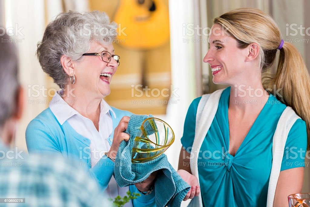 Mother and daughter bond while washing dishes stock photo