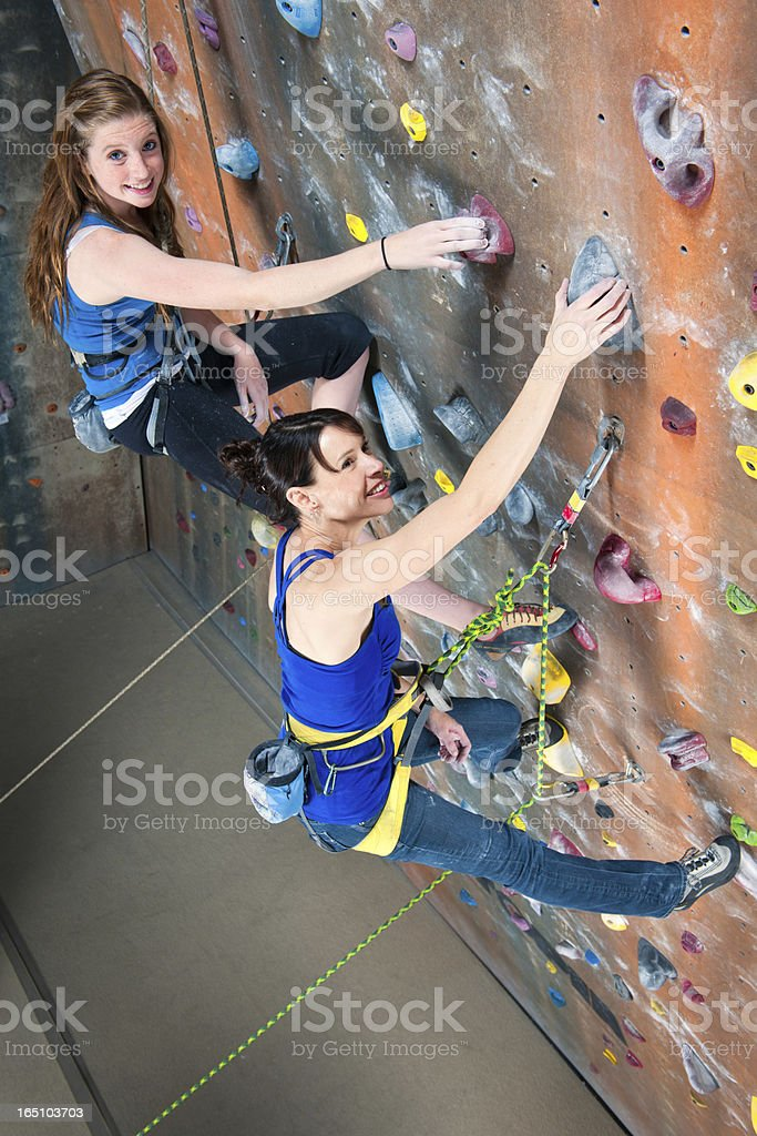 Mother and Daughter Bonding While Indoor Rock Climbing stock photo