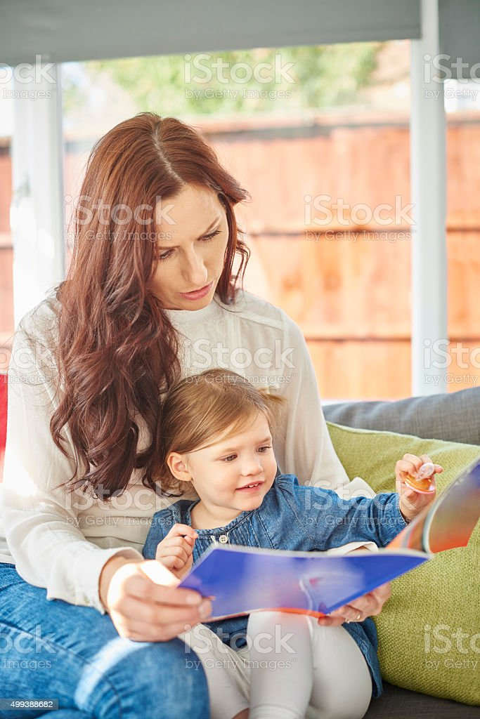 mother and daughter book excitement stock photo