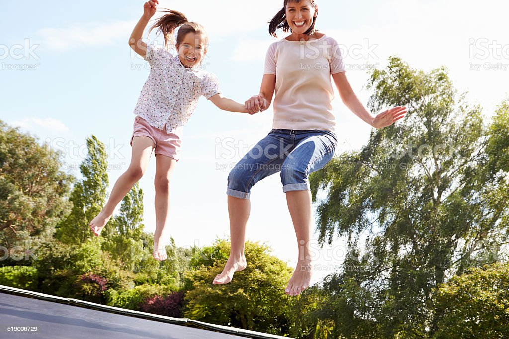 Mother And Daughter Bouncing On Trampoline Together stock photo