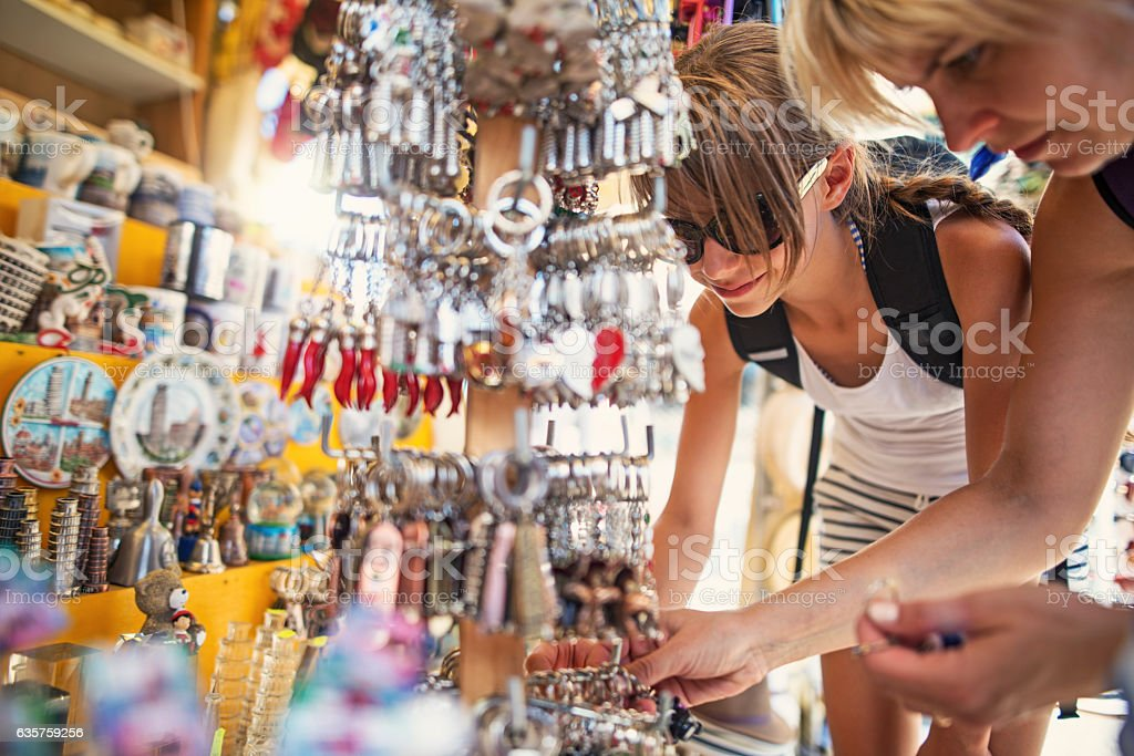 Mother and daughter browsing souvenirs at street market in Pisa stock photo