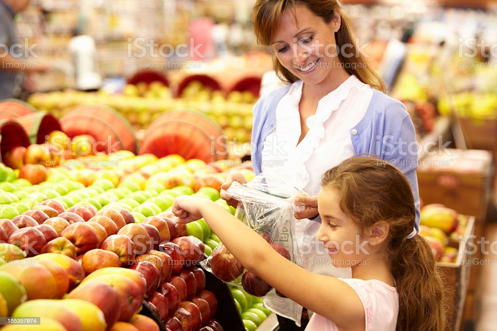 Mother and daughter buying fruit together stock photo