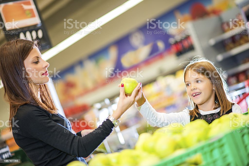 Mother and daughter buying fruit together royalty-free stock photo