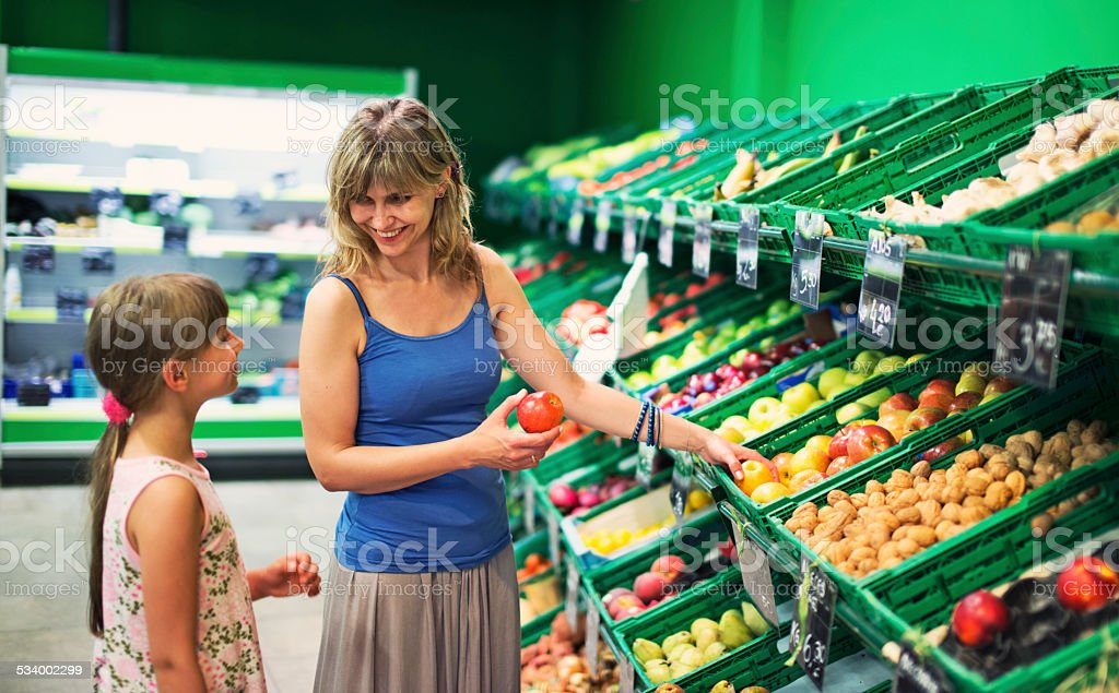 Mother and daughter buying groceries at a supermarket store stock photo