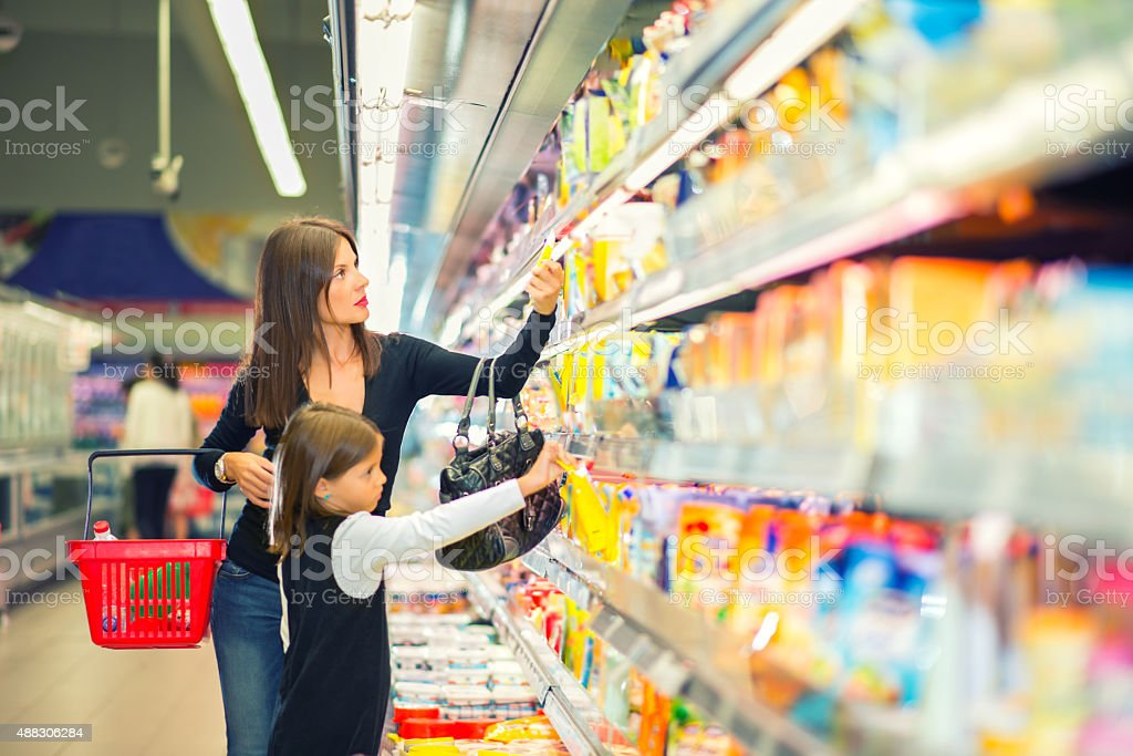 Mother and daughter buying in supermarket stock photo