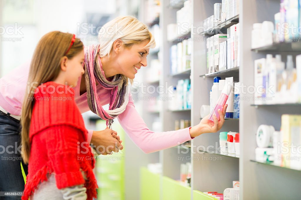 Mother and daughter buying medicine in a pharmacy. stock photo