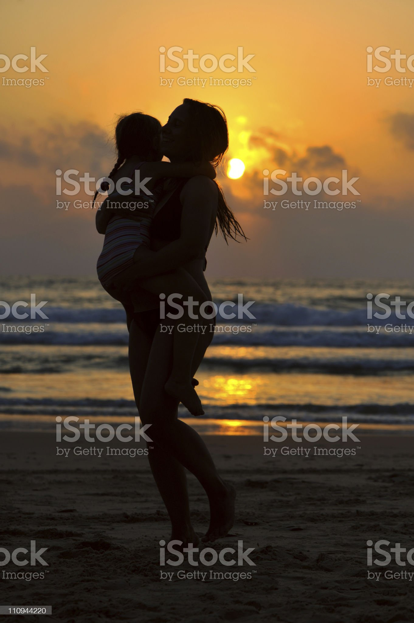 Mother and daughter by the sea at sunset royalty-free stock photo