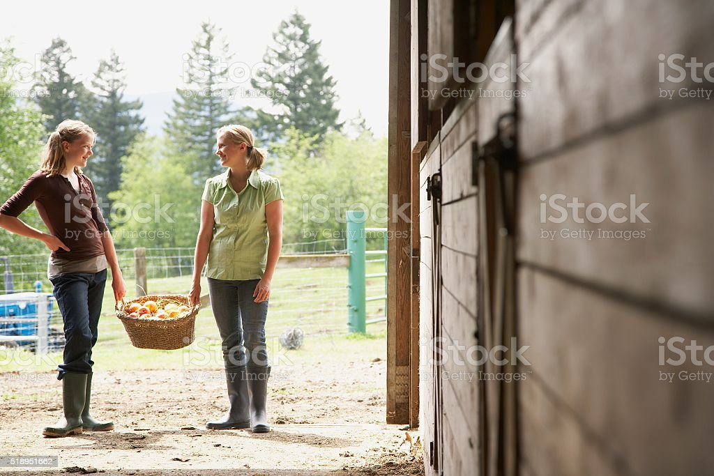 Mother and daughter carrying basket stock photo